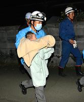 倒壊した家屋から救助された女児を搬送する救急隊員=15日午前3時41分、熊本県益城町、女屋泰之撮影