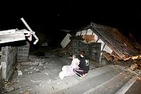 倒壊した家屋の前で座り込む人たち=14日午後11時23分、熊本県益城町、福岡亜純撮影