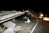 倒壊した家屋の前で座り込む人たち=14日午後11時22分、熊本県益城町、福岡亜純撮影