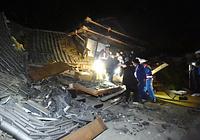 倒壊した家屋に閉じ込められた人を救出する人たち=14日午後11時45分、熊本県益城町惣領、福岡亜純撮影