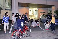 学生寮の外に出て座り込む学生たち=14日午後9時55分、熊本市中央区、福岡亜純撮影