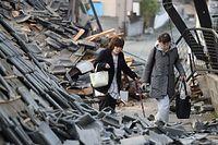屋外の避難所で一夜を過ごし、住宅が倒壊した道路を歩いて自宅に戻る国武ちどりさん(62・左)。「ドンッと突き上げられ、横にも揺さぶられ、怖くて動けなかった」=15日午前6時33分、熊本県益城町宮園、長島