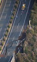 地震で道路が陥没し亀裂の入った九州自動車道=15日午前6時52分、熊本市、朝日新聞社ヘリから、森下東樹撮影