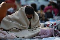 屋外の避難所で一夜を過ごし、毛布で寒さをしのぐ女性=15日午前5時55分、熊本県益城町、長島一浩撮影