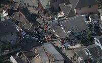 倒壊した家屋の近くでは消防隊員らが活動していた=15日午前8時51分、熊本県益城町、朝日新聞社ヘリから、高橋雄大撮影