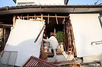 地震で倒壊しかけた家から、生活必需品などを探し出す人の姿があった=15日午前6時40分、熊本県益城町、金川雄策撮影