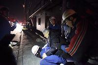 動けない被災者を救助し、避難先に向かう消防団員ら=15日午前1時42分、熊本県益城町安永、福岡亜純撮影