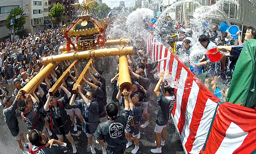 写真:みこし行列の担ぎ手たちに、沿道から水が掛けられる=東京都江東区
