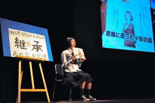 被爆体験を伝えるマンガについて紹介する五日市(広島)の番組が、会場で流された。放送部員が持っているのは印刷したマンガ=長崎県諫早市