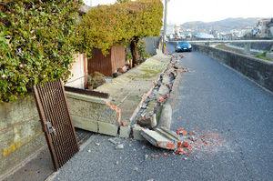 写真:地震の揺れで道路側に倒れた民家のブロック塀=午前5時56分、兵庫県洲本市上物部、吉田博行撮影