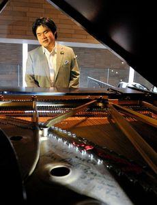 写真:バン・クライバーンさんのサイン(手前)の入ったピアノを弾く辻井伸行さん=18日午後、大阪市北区、高橋一徳撮影