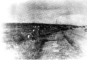 写真:土地接収直後の伊佐浜集落。道路左側には有刺鉄線が張られ、米兵が歩いている=1955年7月19日、沖縄県宜野湾市教育委員会提供