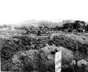 写真:土地接収後の伊佐浜集落。米軍のブルドーザーが田んぼだった土地をならしている=1955年7月、沖縄県宜野湾市教育委員会提供