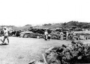 写真:土地接収直後の伊佐浜集落。民家はブルドーザーに押しつぶされた=1955年7月19日、沖縄県宜野湾市教育委員会提供