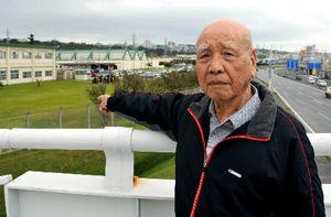 写真:「本土の人には、屈辱を忘れられない人間が沖縄にいることを知ってほしい」。奪われた土地付近を指さす沢岻安一さん=沖縄県北谷町