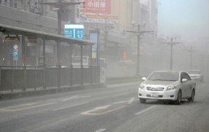 写真:降灰でかすむ鹿児島市中心部を、灰が積もったまま走る車=18日午後5時43分、鹿児島市、滝沢文那撮影(画像を一部修整しています)