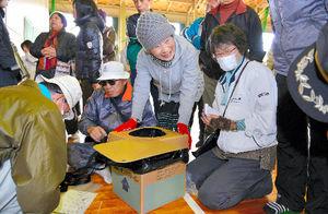 写真:避難所の設営訓練で、簡易トイレを組み立てる住民ら=15日午前10時26分、宮崎市学園木花台南1丁目、中村光撮影