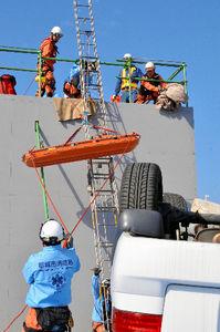 写真:橋の倒壊で車が転落した想定で、救助作業をする消防隊員ら=15日午前11時19分、宮崎市鶴島1丁目、柴田秀並撮影