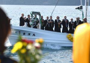 写真:遺族(手前左)らが見守る中、海上で念仏を唱える僧侶たち=4日午後2時52分、宮城県南三陸町の伊里前湾、日吉健吾撮影