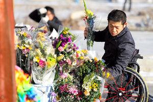 写真:多くの町職員が犠牲になった防災対策庁舎で花を手向ける男性=11日午前7時18分、宮城県南三陸町志津川、越田省吾撮影