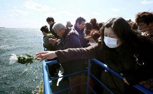 写真:船上から海に向かって献花する人たち=11日午前11時12分、宮城県気仙沼市、西畑志朗撮影
