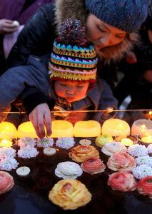 写真:明かりで震災犠牲者を追悼する行事が仮設の商店街で開かれた。子どもたちがろうそくを水に浮かべて手を合わせていた=11日午後5時39分、宮城県石巻市、矢木隆晴撮影