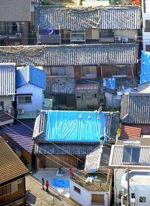 写真:シートで覆うなど、地震で崩れた屋根の応急処置をする人たち=13日午後4時6分、兵庫県洲本市、朝日新聞社ヘリから、森井英二郎撮影