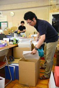 写真:仮役場からの引っ越しのため、書類を段ボールにつめる双葉町の職員=14日午前10時10分、埼玉県加須市の旧騎西高校