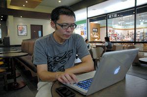 写真:米国からの一時帰国中、実家近くのカフェでツイッターをチェックする竹永浩之さん=3日、熊本県八代市、杉崎慎弥撮影