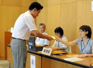 写真:上海の日本総領事館で投票する日本人有権者(左)。投票箱はなく、記入した投票用紙を封筒に入れて職員に渡す。封筒は、白い封筒と、有権者が最後に住民票を置いた日本の自治体の選管あての封筒の二重になっている。さらに、職員が外務省あての封筒に入れる。三重にされた投票用紙は郵送ではなく職員が外務省へ運ぶ=14日午後、中国・上海、今村優莉撮影
