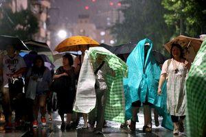 写真:隅田川花火大会が中止となり、シートで雨を避けながら帰る人たち=27日夜、東京都台東区、長島一浩撮影