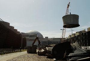 写真:廃炉が決まったドイツ南部のネッカーウェストハイム原発で、冷却塔の煙突を取り除くクレーン=ロイター
