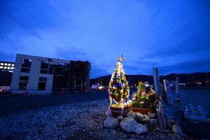 写真:横倒しのビルのそばに点灯したクリスマスツリー=23日夕、宮城県女川町、日吉健吾撮影