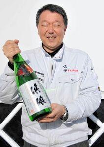 写真:新酒を手に笑顔を見せる古舘秀峰社長=盛岡市の赤武酒造