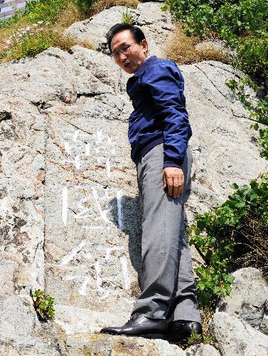 写真:10日、竹島に上陸し、「韓国領」と刻まれた岩の前に立つ李明博大統領=東亜日報提供