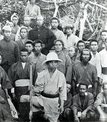 明治時代の尖閣列島。島民と共に記念写真に収まる猟銃を手にした古賀辰四郎=古賀花子さん提供