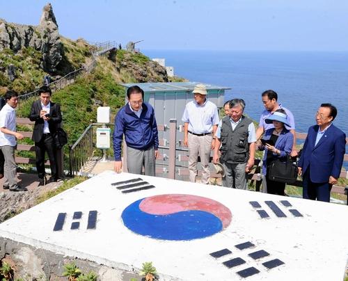 竹島(独島)に上陸し、コンクリート製の韓国国旗の前で説明を受ける李明博大統領(左から3人目)=2012年8月10日、東亜日報提供
