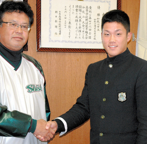 写真:真鍋忠嗣監督(左)と握手する阪口哲也選手=和歌山市六十谷