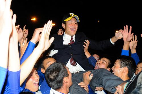 写真:阪神の帽子をかぶり、野球部員に胴上げされ喜ぶ中谷将大捕手=福岡市東区の福岡工大城東