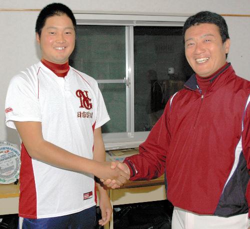 写真:金川豪一郎監督(右)と握手して喜ぶ中崎翔太投手=日南市