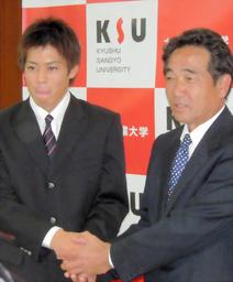写真:指名あいさつに訪れた日本ハムの岩井スカウト(右)と握手する榎下