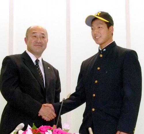 写真:タイガースの帽子をかぶせてもらい、畑山俊二スカウト(左)と握手する岩本輝投手=周南市