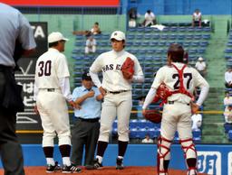 写真:制球が悪く、厳しい表情を浮かべる早大の斎藤(中央)