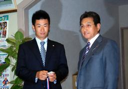 写真:1位指名のあいさつに訪れた阪神・真弓監督(右)からドラフト会場の入場証などを手渡された東京ガスの榎田