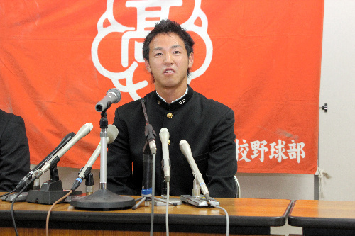 写真:横浜から指名を受け、記者会見で笑顔を見せる渡辺雄貴選手=岡山市北区の関西高校