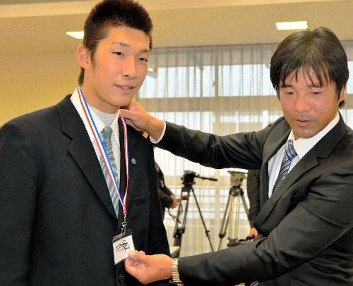 写真:原監督のサイン入りのIDカードを贈られた英明・松本竜也選手(左)=高松市亀岡町