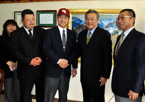 写真:楠城編成部長(右から2人目)と握手を交わす釜田投手=金沢市泉本町3丁目の金沢高校