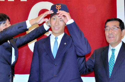 写真:巨人の帽子を初めてかぶり、笑顔を見せる松本投手(中央)=高松市浜ノ町
