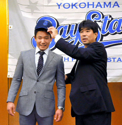 写真:入団契約を終え、横浜のスカウトに帽子をかぶせてもらう松井飛雄馬選手=広島市中区基町