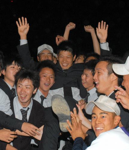 写真:同級生らから胴上げをしてもらい、喜ぶ龍谷高の堤裕貴選手(中央)=佐賀市、上山崎雅泰撮影